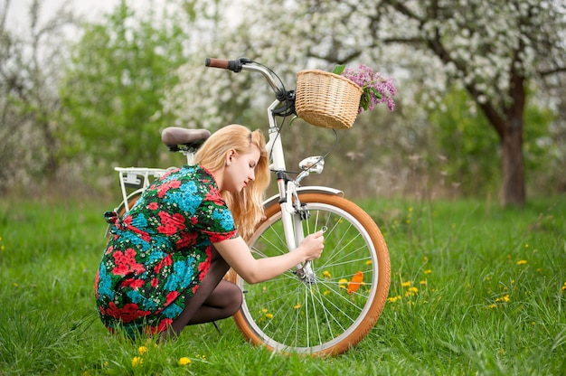 Blonde female in flowered dress repairing her white vintage bicycle in the spring garden