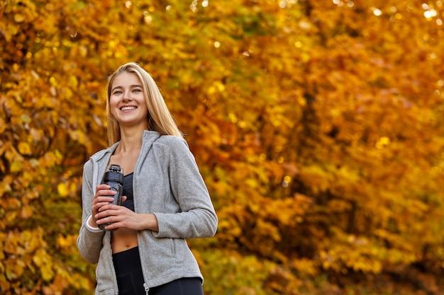 森の中で水のボトルを保持している金髪の女性、肖像画。スポーツウェアのポジティブな女性は、ランニング、ジョギングの後に休息を取ります。晴れた秋の日に