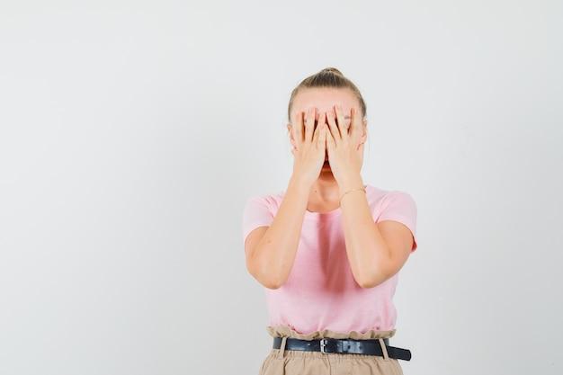 Tシャツ、ズボンで顔に手をつないで、恥ずかしそうに見える金髪の女性。正面図。
