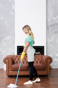 Blonde female housekeeper wiping floor with mop at home