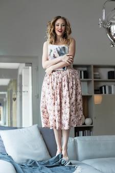 Блондинка в романтическом наряде прыгает на диване босиком, держа в руках журналы