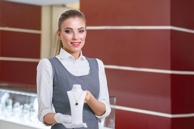 현대 보석 가게에서 예쁜 목걸이를 보여주는 흰 장갑에 금발 여성 보석 노동자