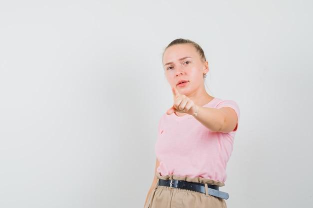 금발 여성 t- 셔츠, 바지 앞에 가리키는 자신감을 찾고. 전면보기.