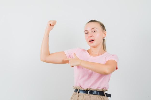 금발 여성 t- 셔츠, 바지에 팔의 근육을 가리키고 자신감을 찾고. 전면보기.