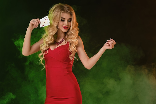 Blonde female in red dress smiling holding something showing two aces posing on colorful smoky backg...