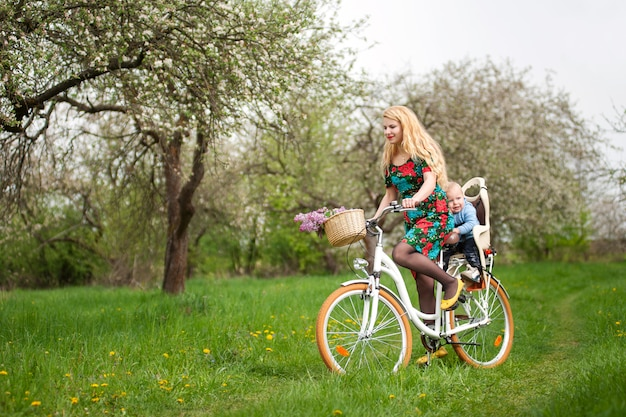 Blonde female riding city bicycle with baby in bicycle chair