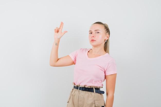 금발 여성 t- 셔츠, 바지에 총 제스처를 표시 하 고 엄격한 찾고. 전면보기.