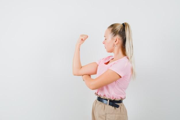 금발 여성 t- 셔츠, 바지에 팔의 근육을 보여주는 자신감을 찾고. 전면보기.