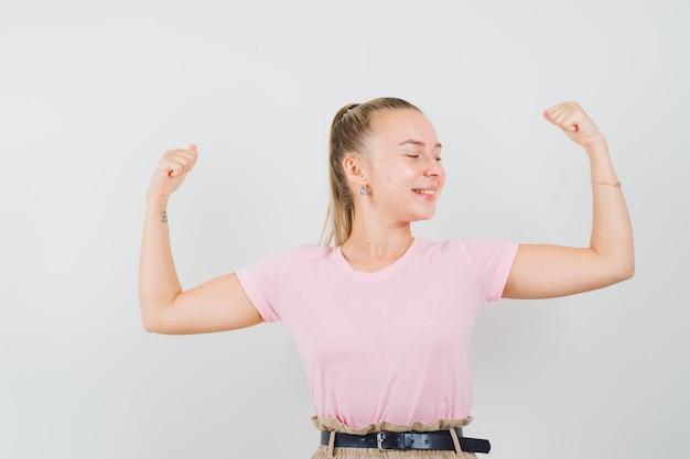 금발 여성 t- 셔츠, 바지에 팔의 근육을 표시 하 고 행복, 전면보기를 찾고.