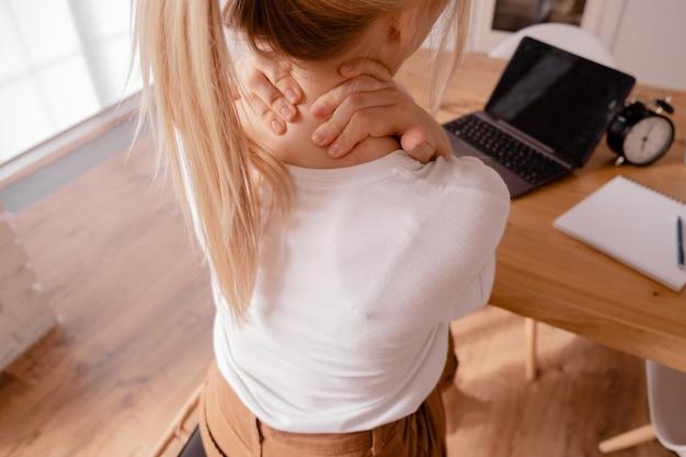 Блондинка женщина сидит за столом и массирует шею.