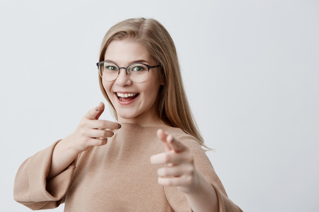 Blonde female in spectacles indicating at you with fingers smiling broadly while having good mood. joyful young cute girl choosing someone, gesturing with hands isolated