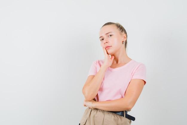생각에 금발 여성 서 t- 셔츠, 바지에 포즈와 현명한, 전면보기를 찾고.
