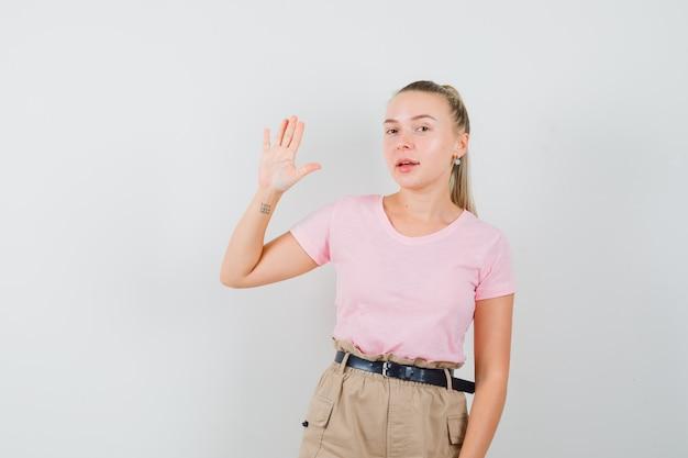 금발 여성 t- 셔츠, 바지에 인사에 대 한 손을 흔들며 좋은, 전면보기를 찾고.