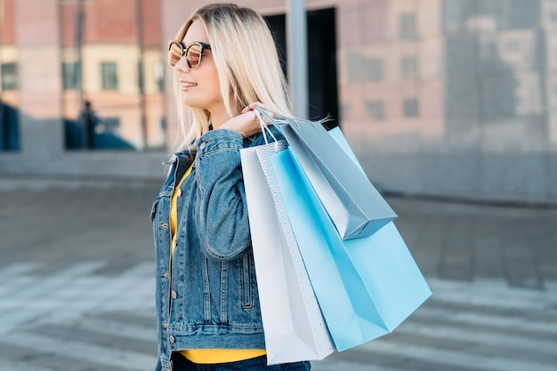 Blonde female with assortment of paper bags in hands