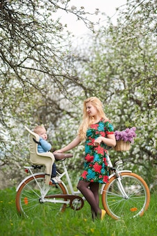 Blonde female with city bicycle with baby in bicycle chair
