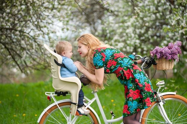 自転車の椅子に赤ちゃんと一緒に街の自転車を持つ金髪の女性