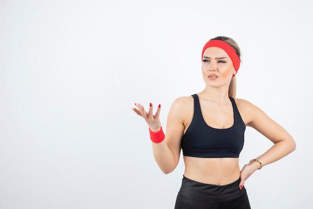 Blonde fit woman in black sportswear posing.