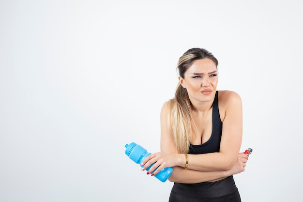 Blonde fit woman in black top standing and holding bottle of water with expander.