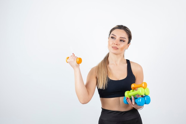 Blonde fit woman in black top standing and holding colorful dumbbells.