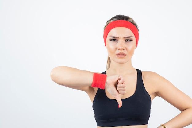 立って親指を下に見せている黒いスポーツウェアの金髪のフィットの女性。