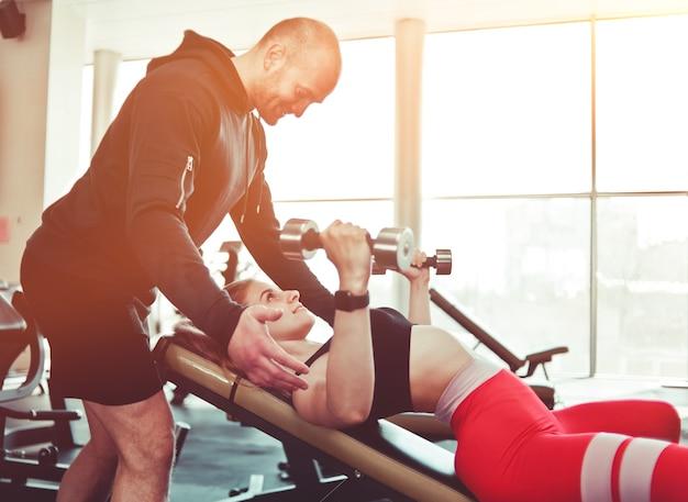 ジムで男性インストラクターのパートナーと傾斜したベンチに横たわってダンベルベンチプレスをしているスポーツウェアの金髪のフィット女性。
