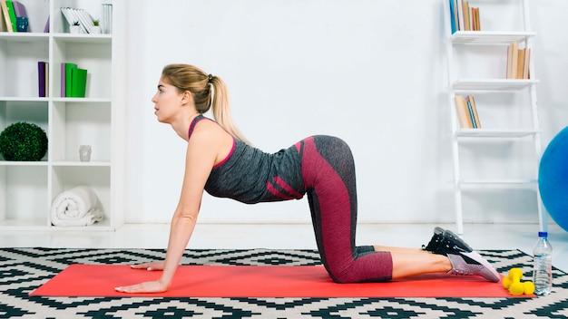 Blonde fit young woman in a neutral cow pose on red exercise mat