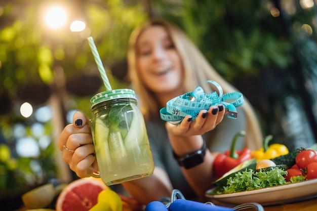 La ragazza bionda si siede sul tavolo e tiene in mano un frullato fresco e misura, concetto di tempo di dieta.