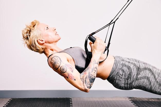 Тренировка блондинки фитнеса с ремнями фитнеса trx