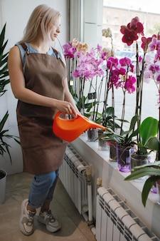 금발의 꽃집 여자 물은 꽃 가게의 작업 공간에서 식물을 돌봅니다. 선택적 초점입니다.