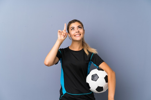 Blonde football player teenager girl over grey wall pointing up a great idea