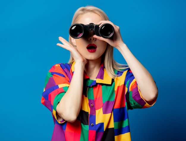 Blonde girl in 90s shirt with binoculars on blue space