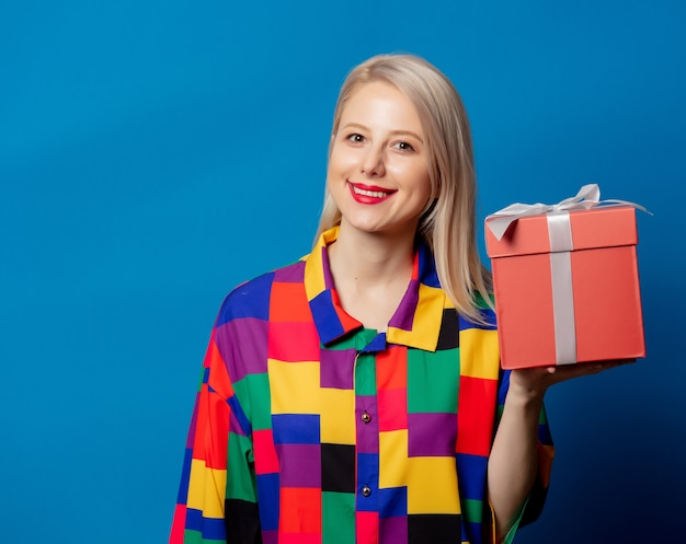 Blonde girl in 90s shirt with shopping bag on blue space