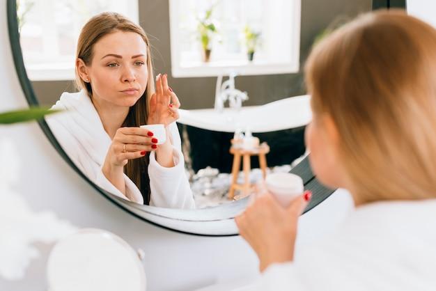 Blonde girl applying cream on her face
