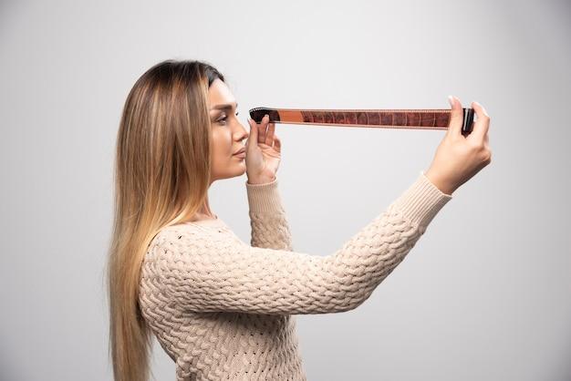 Ragazza bionda che controlla attentamente le foto sul rotolo di foto.