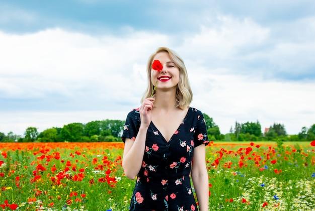 Blonde girl in beautiful dress in poppies field in summer time