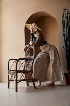 Blonde girl in big straw hat leaning on rattan chair