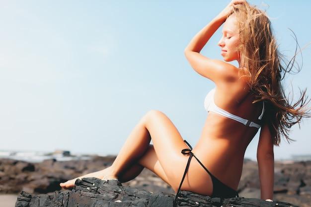Blonde girl in bikini on the summer beach