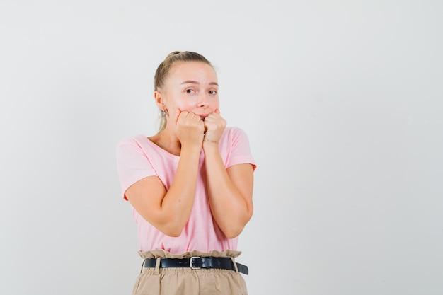 금발 소녀 t- 셔츠, 바지에 감정적으로 주먹을 물고 무서 워보고. 전면보기.