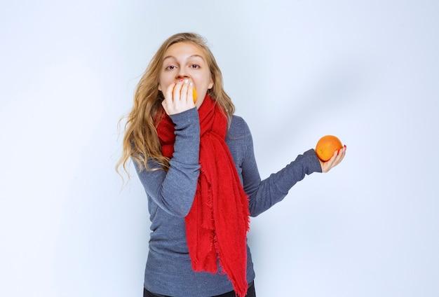 Blonde girl biting a juicy orange fruit.