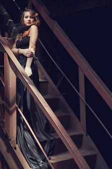 Blonde girl in black dress old abandoned factory