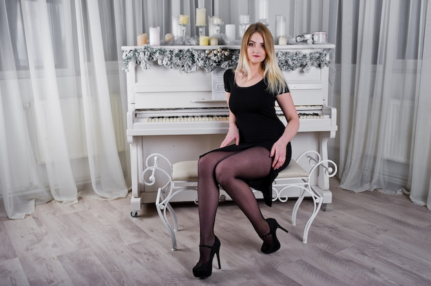 Blonde girl in black dress posed near piano with christmas candles decor in white room.
