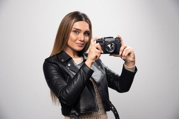 Ragazza bionda in giacca di pelle nera prendendo i suoi selfie con una macchina fotografica.