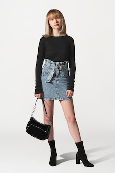 Ragazza bionda in maglione nero e gonna di jeans per un servizio di abbigliamento invernale