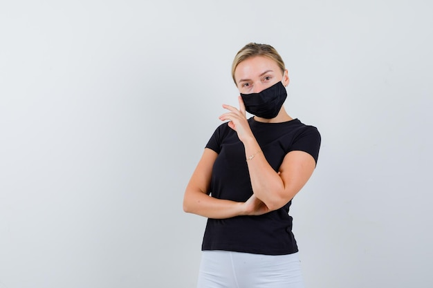 Blonde girl in black t-shirt, white pants, black mask leaning isolated