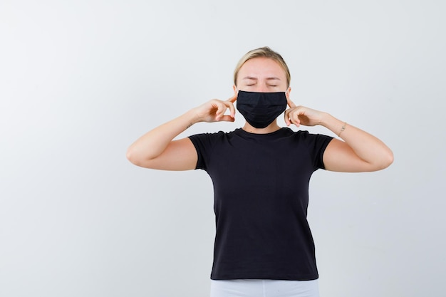 Ragazza bionda in maglietta nera, pantaloni bianchi, maschera nera che tappa le orecchie isolate