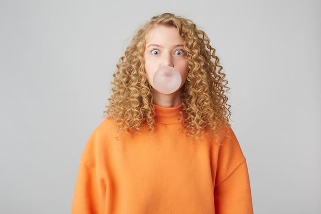 チューインガムで泡を吹くブロンドの女の子は、白い壁の上に孤立して立っている暖かい明るいオレンジ色の特大のセーターを着ています