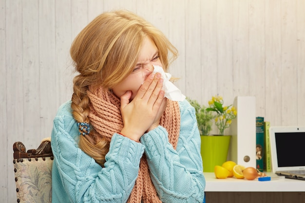A blonde girl blows her nose in a handkerchief at home, against the  of a table on which lies an onion and lemons, books and a laptop