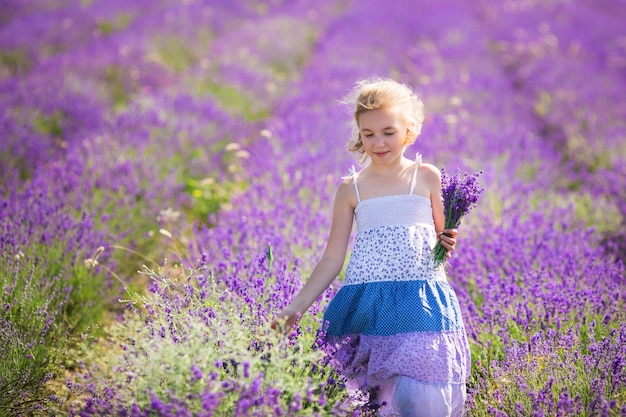Blonde girl in the blue dress in the field of lavander with a small bouqet of flower