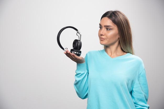 Ragazza bionda in felpa blu che tiene le cuffie e si prepara a indossarle per ascoltare la musica.