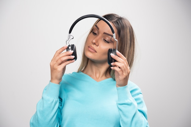 Blonde girl in blue sweatshirt holding headphones and gets ready to wear them to listen to the music